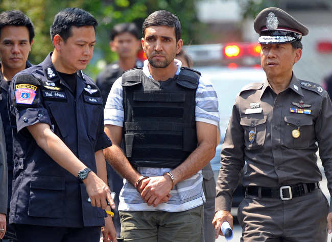 เจ้าหน้าที่ตำรวจไทยคุมตัวผู้ต้องสงสัยวางระเบิดชาวอิหร่าน นายโมฮัมหมัด คาซาอี (กลาง) ระหว่างการสอบสวน ที่บ้านเช่าของเขา ในกรุงเทพฯ เมื่อวันที่ 20 กุมภาพันธ์ 2555 (เอเอฟพี)