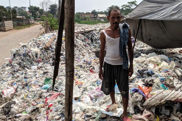 ชาวบ้านยืนอยู่บนกองขยะพลาสติกนำเข้าปริมาณหลายตัน ที่พื้นที่ทิ้งขยะ เมืองเบกาซี ทางชวาตะวันตก ประเทศอินโดนีเซีย วันที่ 16 พฤษภาคม 2561  (อัฮหมัด ไซยัมซูดิน/เบนาร์นิวส์)