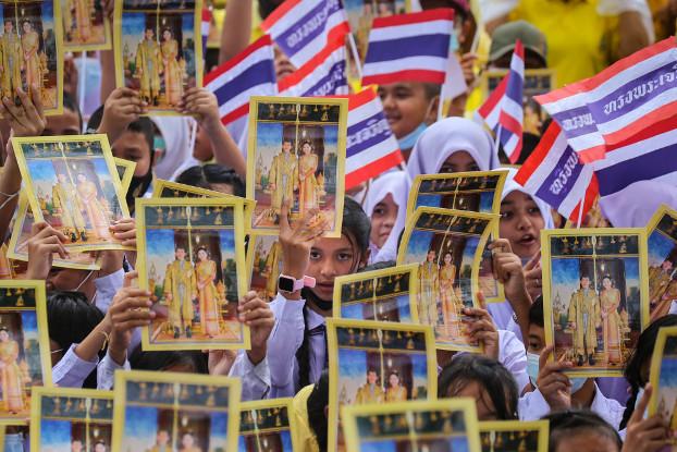 """นักเรียนชูพระบรมฉายาลักษณ์ของพระบาทสมเด็จพระเจ้าอยู่หัว และสมเด็จพระนางเจ้าฯ พระบรมราชินี พร้อมโบกธงชาติไทย ขณะร่วมกิจกรรม """"รวมพลคนปัตตานี ปกป้องสถาบันชาติ ศาสนา พระมหากษัตริย์"""" หน้าศาลากลางจังหวัดปัตตานี วันที่ 22 ตุลาคม 2563 (เอเอฟพี)"""
