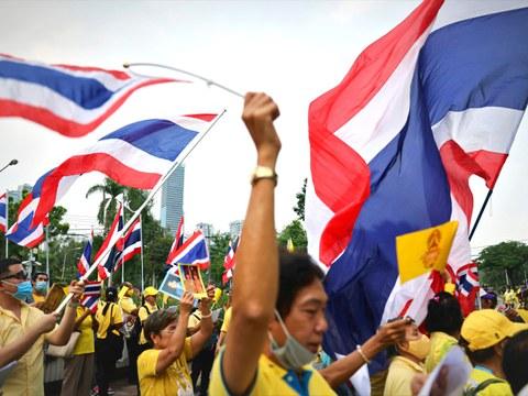 กลุ่มประชาชนสวมเสื้อเหลืองโบกธงชาติไทย ขณะเดินประท้วงเพื่อสนับสนุนสถาบันพระมหากษัตริย์ ในกรุงเทพฯ วันที่ 27 ตุลาคม 2563