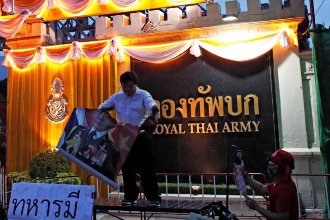 นักเคลื่อนไหวต่อต้านรัฐบาลฉีกรูปพลเอก อภิรัชต์ คงสมพงษ์ ระหว่างการประท้วง หน้ากองทัพบก กรุงเทพฯ วันที่ 20 กรกฎาคม 2563