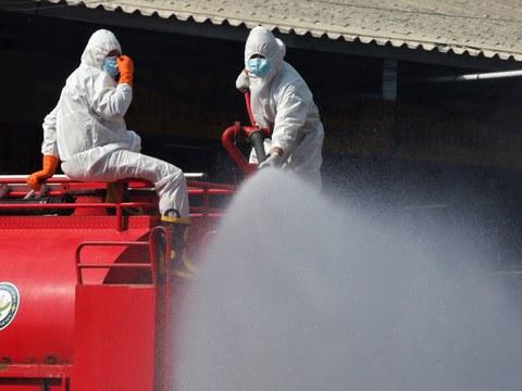 คนงานฉีดพ่นยาฆ่าเชื้อ เพื่อป้องกันการแพร่ระบาดไวรัสโคโรนา ที่ตลาดกุ้ง จังหวัดสมุทรสาคร วันที่ 25 มกราคม 2564