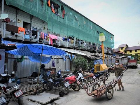 ผู้หญิงเข็นรถนอกแคมป์ที่พักของคนงานก่อสร้างไทยและเมียนมา ซึ่งอยู่ภายใต้มาตรการล็อกดาวน์ป้องกันโควิด-19 หนึ่งเดือนของรัฐ เขตหลักสี่ กรุงเทพฯ วันที่ 28 มิถุนายน พ.ศ. 2564