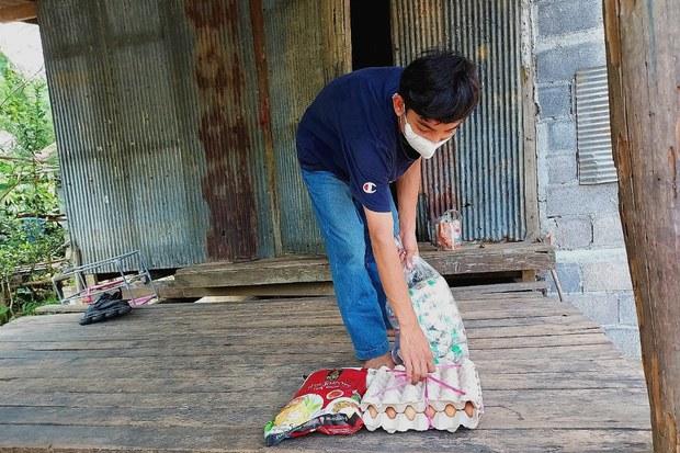 ด.ช.อุสมัน (ขอสงวนนามสกุล) ในบ้านลาแล ต.กาบัง จ.ยะลา รับอาหารและยาสำหรับผู้กักตัวเพราะติดเชื้อโควิด-19 ด้วยความดีใจ วันที่ 18 ตุลาคม 2564