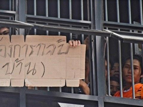 แรงงานเมียนมาที่ถูกควบคุมตัว ชูป้ายขอกลับบ้าน ที่ห้องกัก สำนักงานตรวจคนเข้าเมืองจังหวัดระนอง วันที่ 25 มกราคม 2564