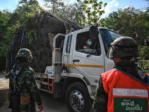 เจ้าหน้าที่ทหารไทยตรวจเช็คคนขับรถบรรทุกวัสดุก่อสร้างขณะผ่านด่านตรวจ บนถนนมุ่งสู่แม่น้ำสาละวิน ที่ชายแดนไทย-เมียนมา ในจังหวัดแม่ฮ่องสอน วันที่ 1 พฤษภาคม พ.ศ. 2564